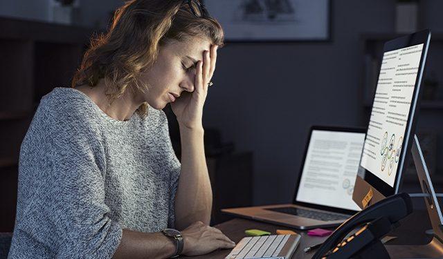 Junge Frau mit Burnout am Arbeitsplatz