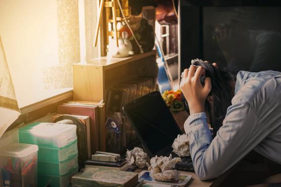 Junge Frau überfordert und gestresst am Arbeitsplatz
